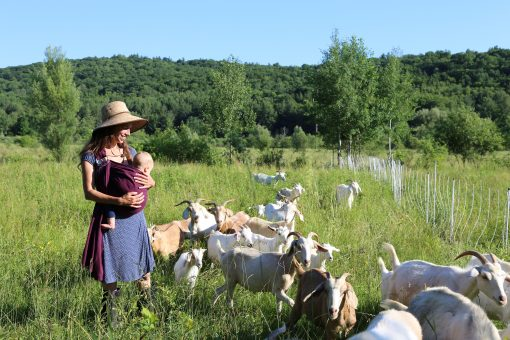 Marleen in the field with the goats and baby