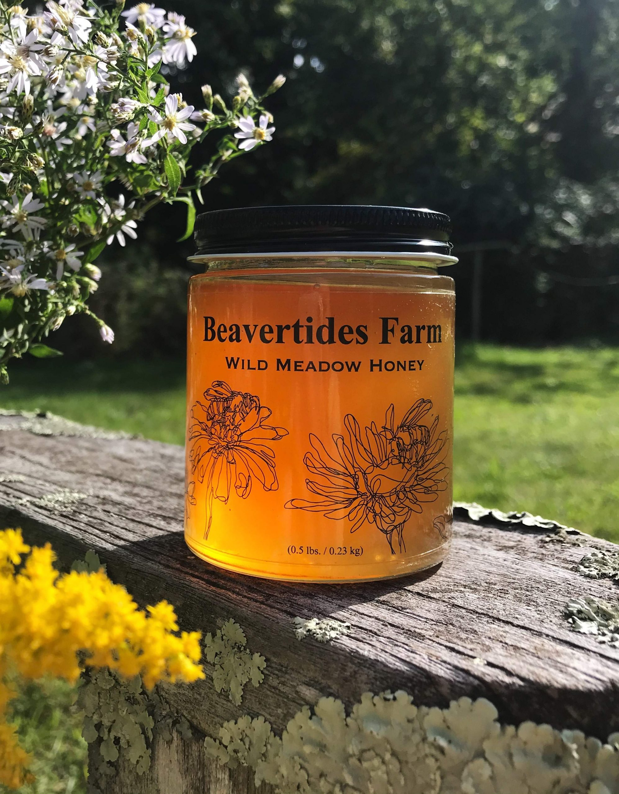 Honey jar outside with flowers