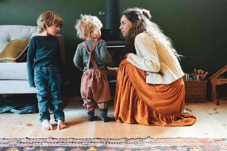 Mama and two boys in front of the wood stove