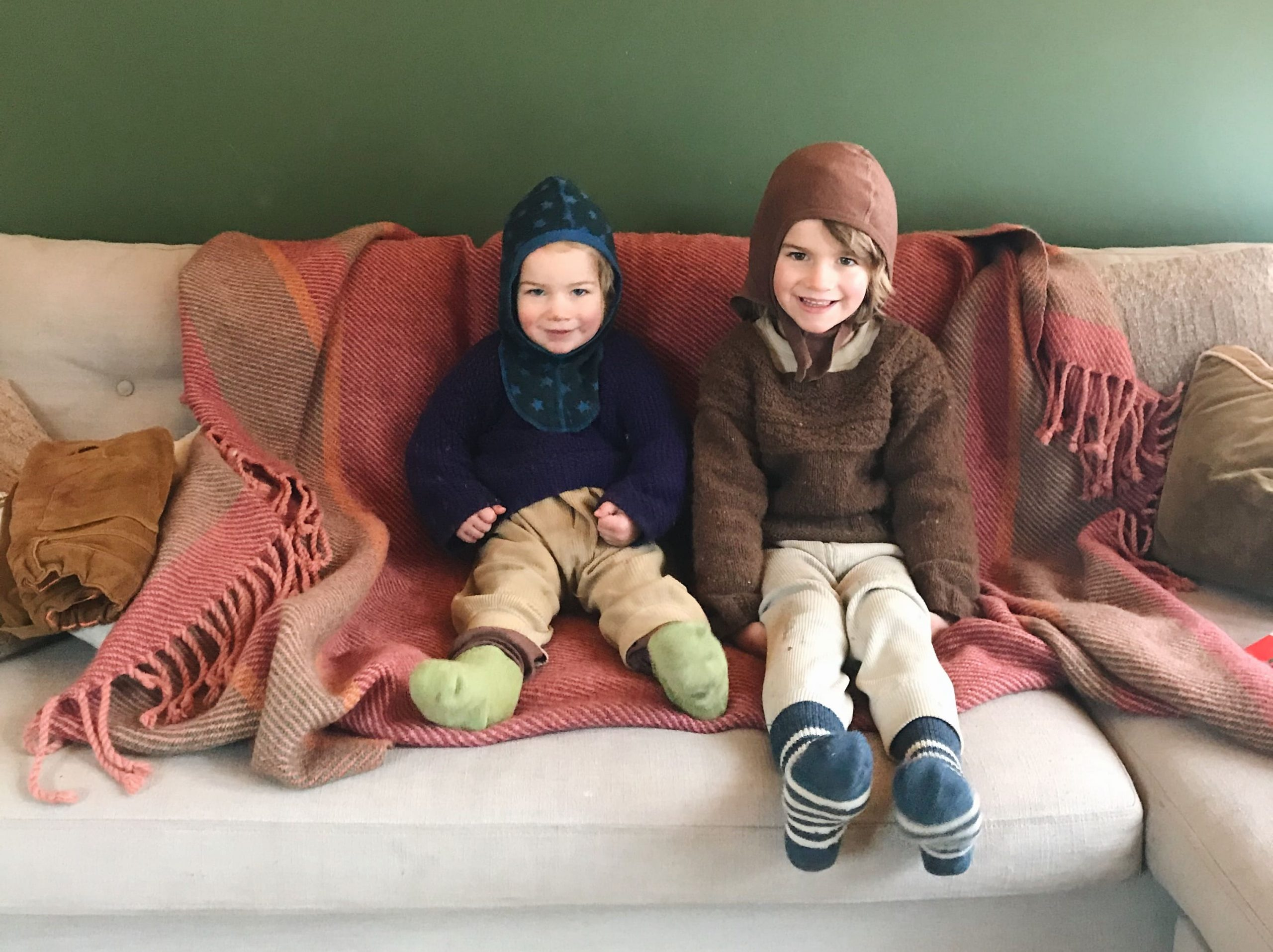 Two boys dressed in wool on couch