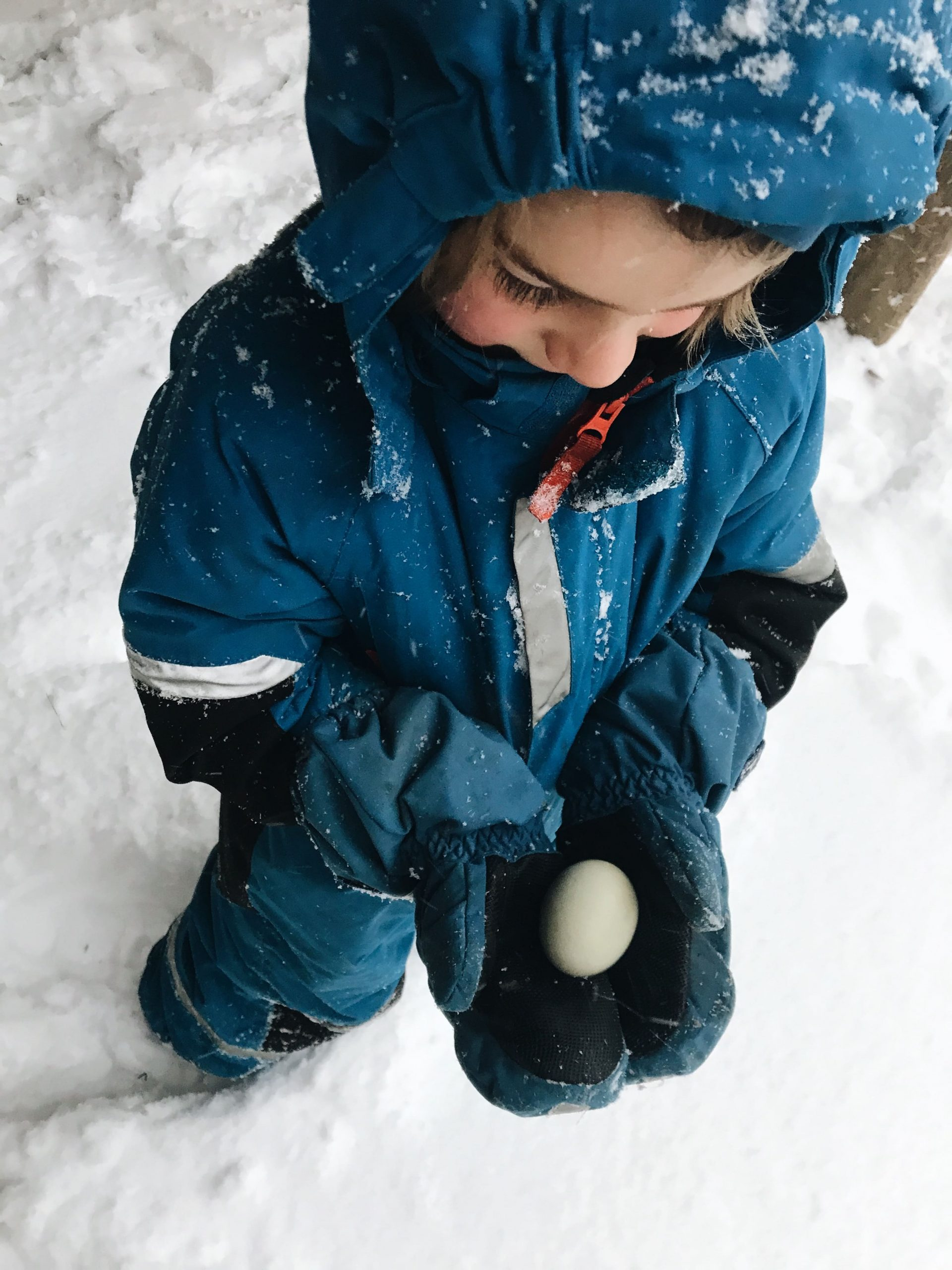 Little boy in snow with egg in hands