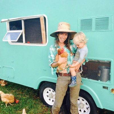 Mother holding child and pasture raised backyard layer chicken